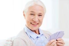 Карточки счастливой старшей женщины играя дома Стоковая Фотография