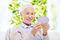 Карточки счастливой старшей женщины играя дома Стоковое фото RF