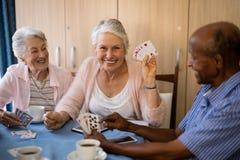 Карточки счастливых старших людей играя пока имеющ кофе Стоковое Изображение