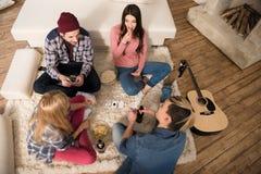 Карточки людей и женщин играя и есть попкорн дома Стоковые Фото