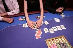 Карточный игрок проверяет руку стоковое фото