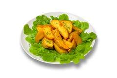 Картошка заклинивает с салатом на плите на белой предпосылке стоковые изображения