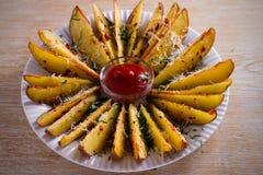 Картошка испеченная чесноком заклинивает с паприкой и сыр пармесаном Фраи картошки на белой плите Стоковое фото RF
