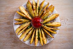 Картошка испеченная чесноком заклинивает с паприкой и сыр пармесаном Фраи картошки на белой плите Стоковая Фотография