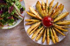 Картошка испеченная чесноком заклинивает с паприкой и сыр пармесаном Фраи картошки на белой плите Стоковая Фотография RF
