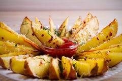 Картошка испеченная чесноком заклинивает с паприкой и сыр пармесаном Фраи картошки на белой плите Стоковое Изображение RF