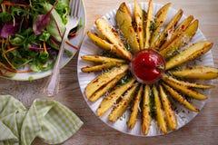 Картошка испеченная чесноком заклинивает с паприкой и сыр пармесаном Фраи картошки на белой плите Стоковое Фото