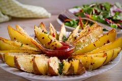 Картошка испеченная чесноком заклинивает с паприкой и сыр пармесаном Фраи картошки на белой плите Стоковые Изображения RF