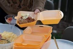 Картошка куртки сервировки женщины и свои отбензинивания в коробку для завтрака взятия отсутствующую стоковые фото