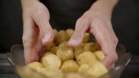 Картошка mixex человека со специями и оливковым маслом в шаре в темной кухне видеоматериал