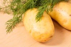 Картошки и укроп на доске кухни Стоковая Фотография