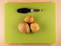 3 картошки и peeler на зеленой пластичной доске Стоковая Фотография RF