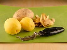 3 картошки и peeler на используемой зеленой доске Стоковые Фото