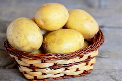 картошки сырцовые Молодые сырцовые картошки в плетеной корзине изолированной на старой деревянной предпосылке closeup Стоковые Изображения RF