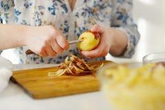 Картошки шелушения молодой женщины с ножом Стоковые Изображения