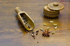 Кардамон на таблице, перец анисовки звезды в деревянной ложке Стоковые Фото