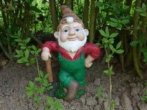 Карлик с лопаткоулавливателем в его саде Стоковое фото RF