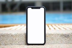 Касайтесь телефону с изолированным экраном на предпосылке бассейна Стоковое фото RF