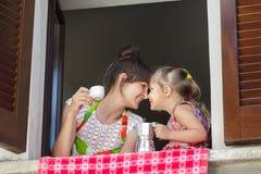 Касаться с матерью носов и ее 2 летами старой дочери держа традиционный итальянский комплект кофе белых чашки и металла Стоковые Фото