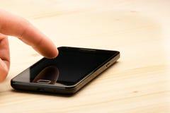 касатьться smartphone экрана черной руки Стоковое фото RF