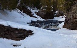 Каскадируйте река в северной Минесоте высекая свой путь через лед и снег стоковые фото