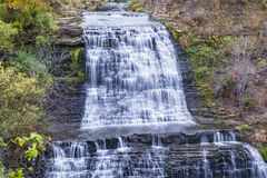 Каскадируя водопад в уровнях бежать через скалистый заросший лесом lan Стоковые Изображения RF
