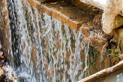 Каскадировать воды пропуская над ровным утесом Стоковые Изображения