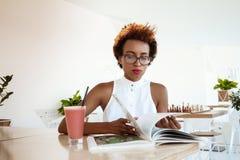 Кассета чтения smoothie красивой африканской девушки выпивая отдыхая в кафе Стоковые Фотографии RF