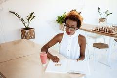 Кассета чтения smoothie красивой африканской девушки выпивая отдыхая в кафе Стоковое Изображение RF