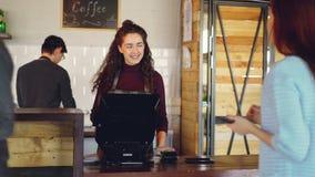 Кассир привлекательной женщины словоохотливый признавает безконтактные оплаты с мобильным телефоном и говорит к клиентам и акции видеоматериалы