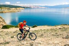 Катание велосипедиста горы на велосипеде в древесинах захода солнца лета Стоковое фото RF