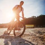 Катание велосипедиста вдоль пляжа на заходе солнца Стоковые Фотографии RF