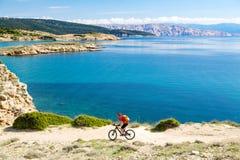 Катание велосипедиста горы на велосипеде в древесинах захода солнца лета Стоковое Изображение