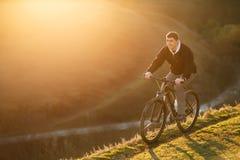 Катание велосипедиста на верхней части холма и наблюдать взгляд Стоковая Фотография