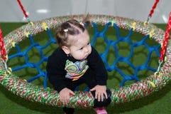 Катание девушки ребенка на качании на спортивной площадке в торговом центре Стоковое Изображение RF