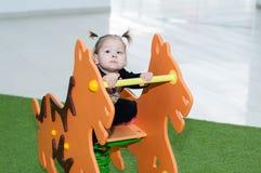 Катание девушки ребенка на качании на спортивной площадке в торговом центре Стоковое Изображение
