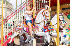 Катание девушки на веселом идет круг Маленькая девочка играя на carousel, потехе лета, счастливом детстве и концепции каникул Стоковые Изображения RF