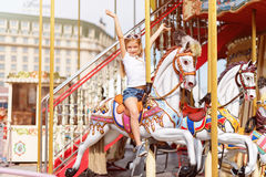 Катание девушки на веселом идет круг Маленькая девочка играя на carousel, потехе лета, счастливом детстве и концепции каникул Стоковая Фотография