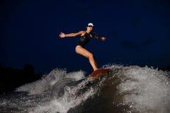 Катание женщины взгляда со стороны молодое активное на wakesurf в ноче стоковое изображение rf