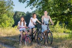 Катание женщины с дочерьми на велосипедах на поле Стоковое фото RF