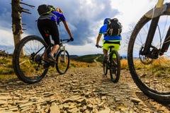 Катание женщин и человека горы велосипед на велосипедах на горе захода солнца Стоковая Фотография