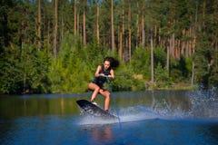 Катание исследования молодой женщины wakeboarding на озере Стоковое Изображение