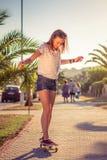 Катание маленькой девочки в скейтборде outdoors дальше Стоковая Фотография RF