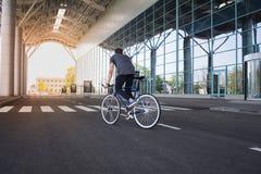 Катание молодого человека на велосипеде в улице города Человек на голубом велосипеде с белыми колесами, большой предпосылке окон  Стоковые Изображения