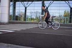 Катание молодого человека на велосипеде в улице города Человек на голубом велосипеде с белыми колесами, большой предпосылке окон  Стоковые Фотографии RF