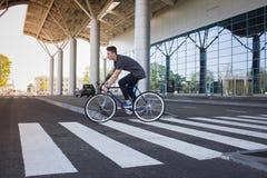 Катание молодого человека на велосипеде в улице города Человек на голубом велосипеде с белыми колесами, большой предпосылке окон  Стоковое Изображение
