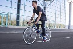 Катание молодого человека на велосипеде в улице города Человек на голубом велосипеде с белыми колесами, большой предпосылке окон  Стоковая Фотография RF