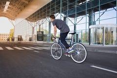 Катание молодого человека на велосипеде в улице города Человек на голубом велосипеде с белыми колесами, большой предпосылке окон  Стоковое фото RF
