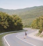 Катание молодого человека на longboard на дороге Стоковые Фотографии RF