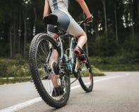 Катание молодой женщины на велосипеде горы около леса стоковое фото